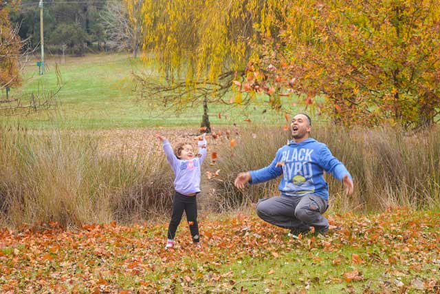 Em and Rick throwing autumn leaves over their head.