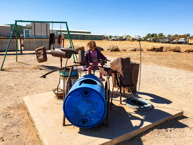 lala making music on some of the junk at Winton's musical fence